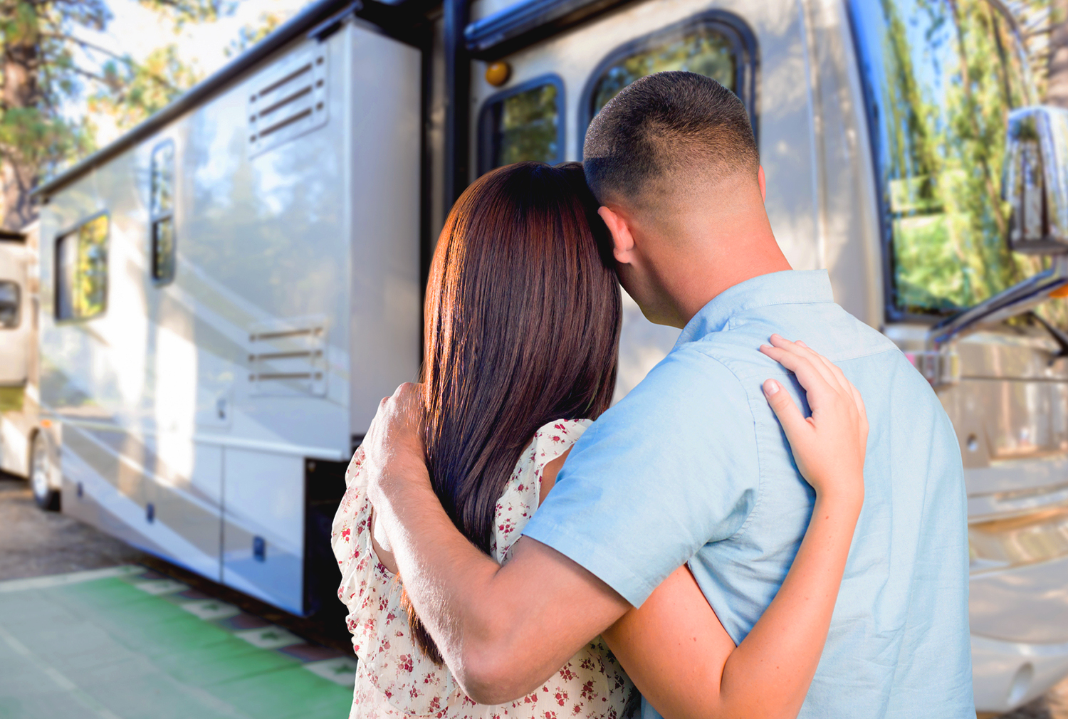 Young couple hugging in front of their large camper van motorhome after an RV Inspection
