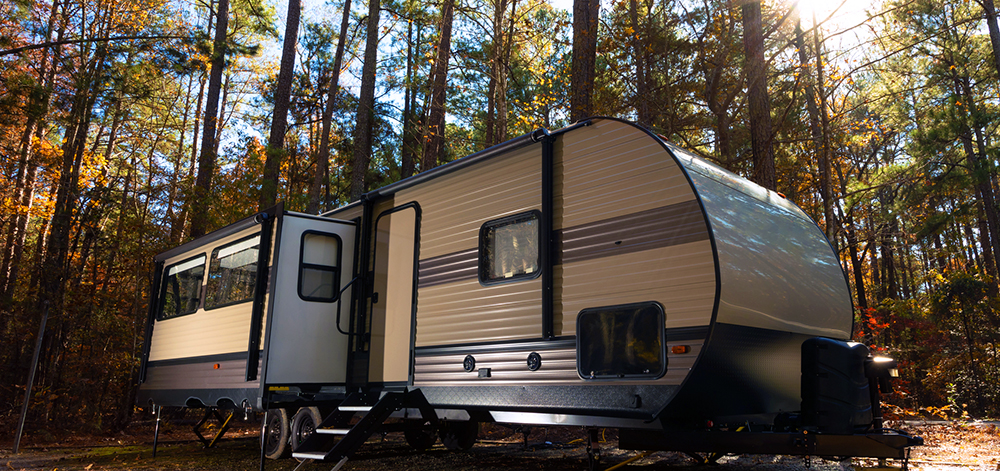 Camper trailer parked in a forest in autumn after being thoroughly checked by our rv inspectors