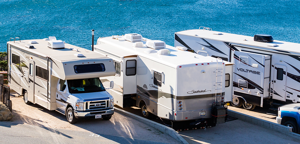 Multiple types of motorhomes parked by the beach after an rv inspection