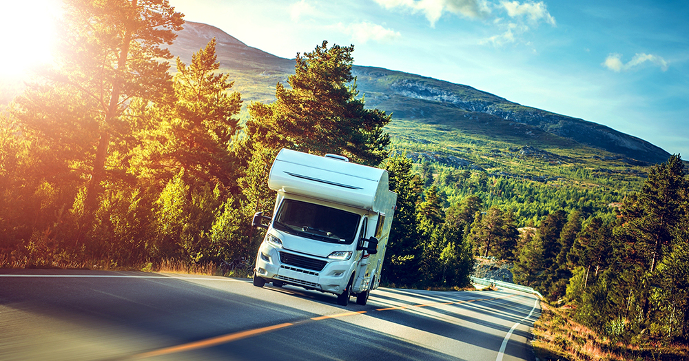 Camper van motorhome driving on a mountain road after thorough RV inspection services